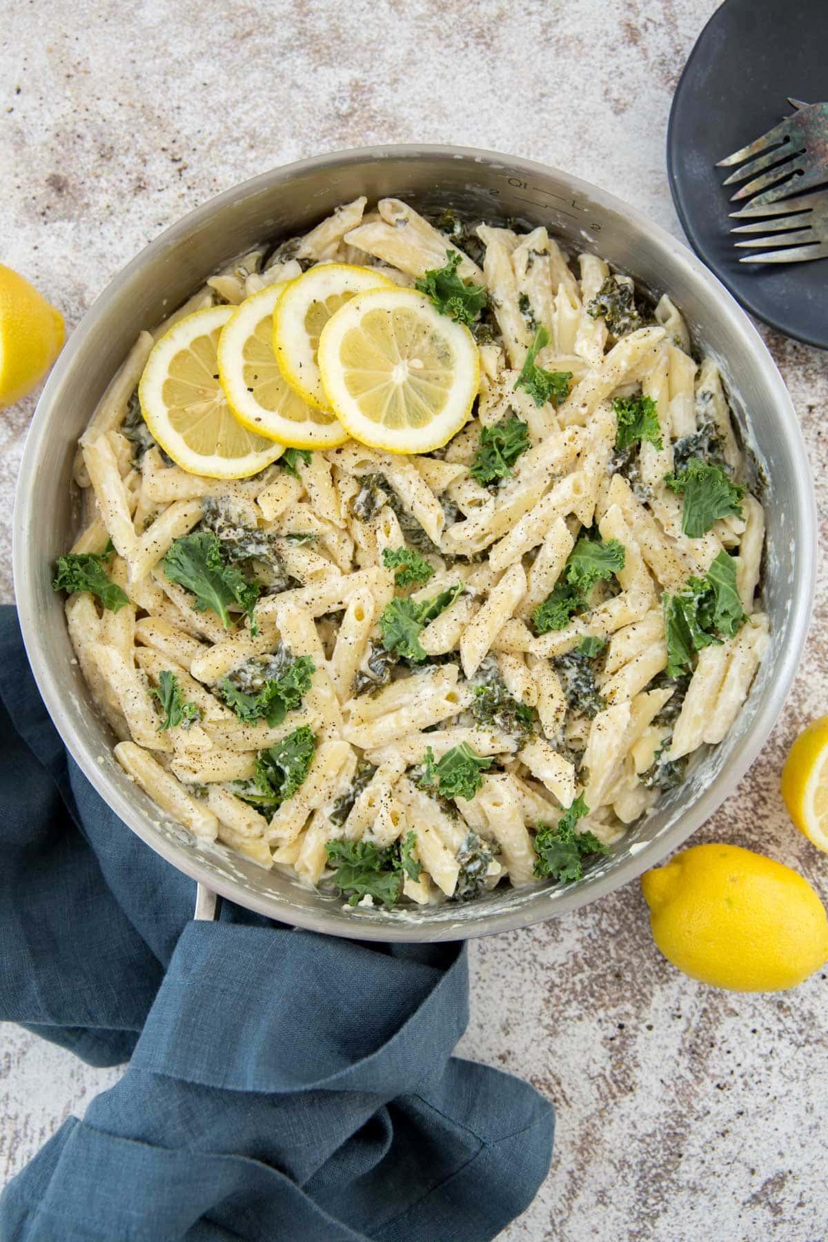 large silver saute pan, pasta, kale, lemon, blue napkin