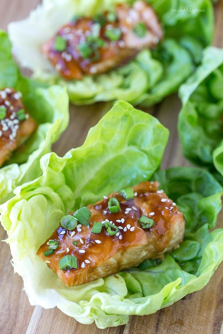 A wood cutting board with lettuce cups holding pieces of salmon with teriyaki sauce. They are garnished with sesame seeds and green onions.