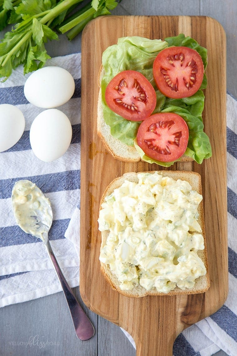 egg salad sandwich open faced with lettuce and tomato