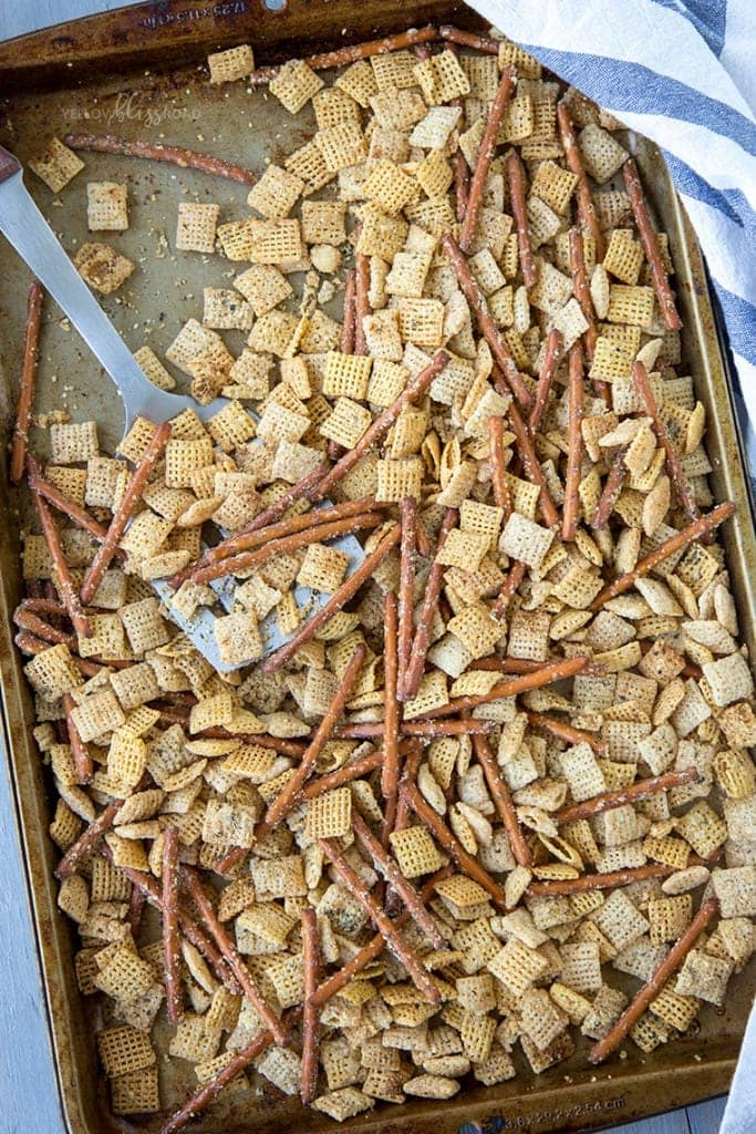 chex mix on a baking sheet with a spatula