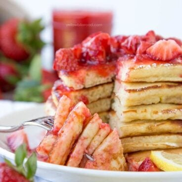 A plate of pancakes with strawberries on top