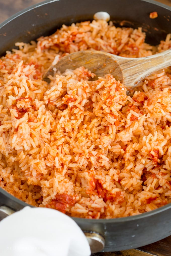 Authentic restaurant style Mexican Rice, being fluffed in the pan with a spoon