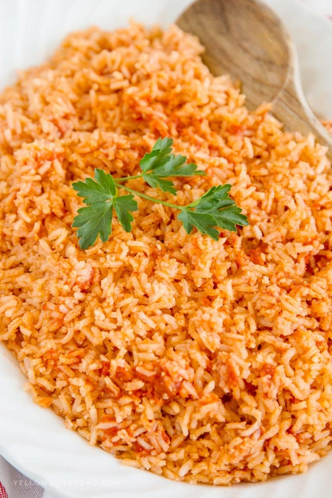Authentic Mexican Rice recipe on a platter with a wooden spoon, a sprig of parsley