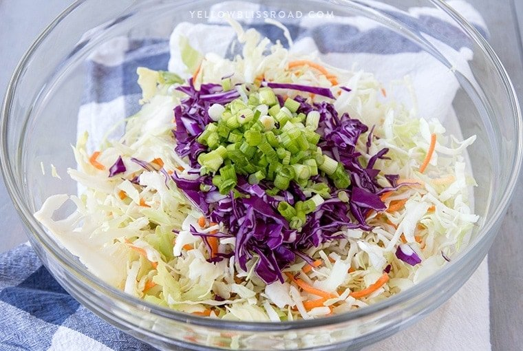 a glass bowl with coleslaw mix and green onions