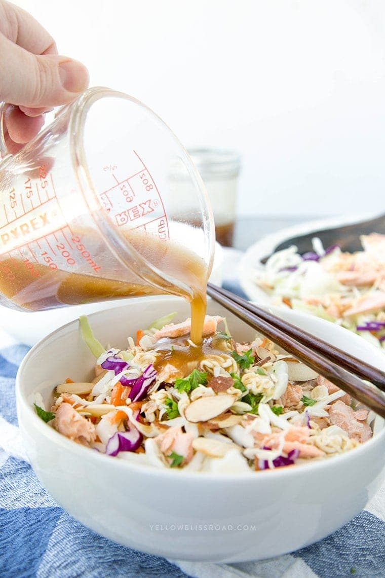 Asian dressing being poured over a bowl of ramen noodle salad