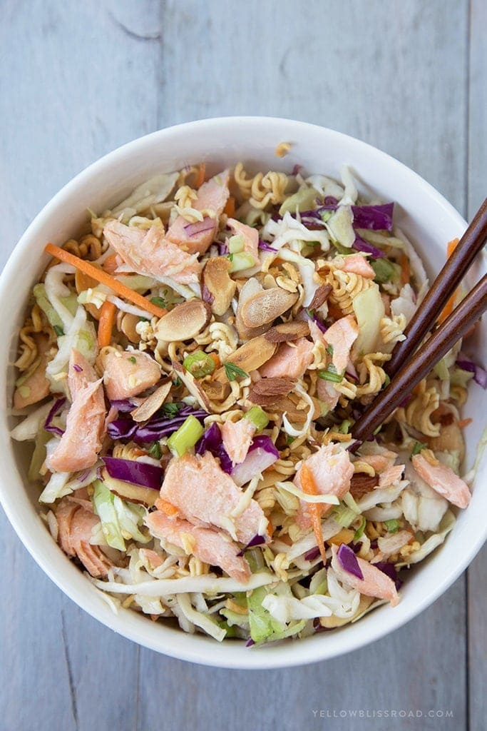 A serving sized bowl of ramen noodle salad with salmon