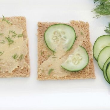 A close up of Hummus and Cucumbers on bread