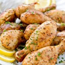 baked chicken drumsticks, white platter, parsley, lemon slices