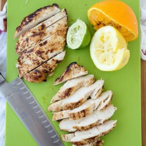A cutting board with grilled chicken and citrus fruits