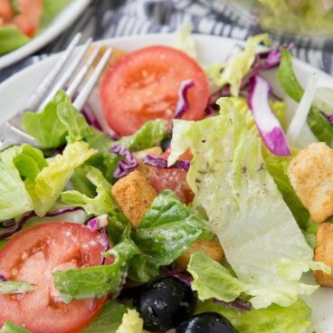 A close up of Olive Garden salad with tomatoes and croutons
