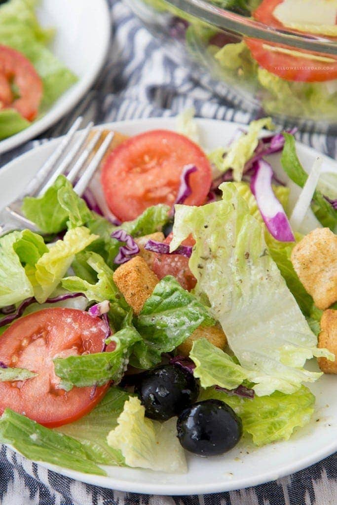 A close up of a salad with tomatoes, olive, onions and croutons