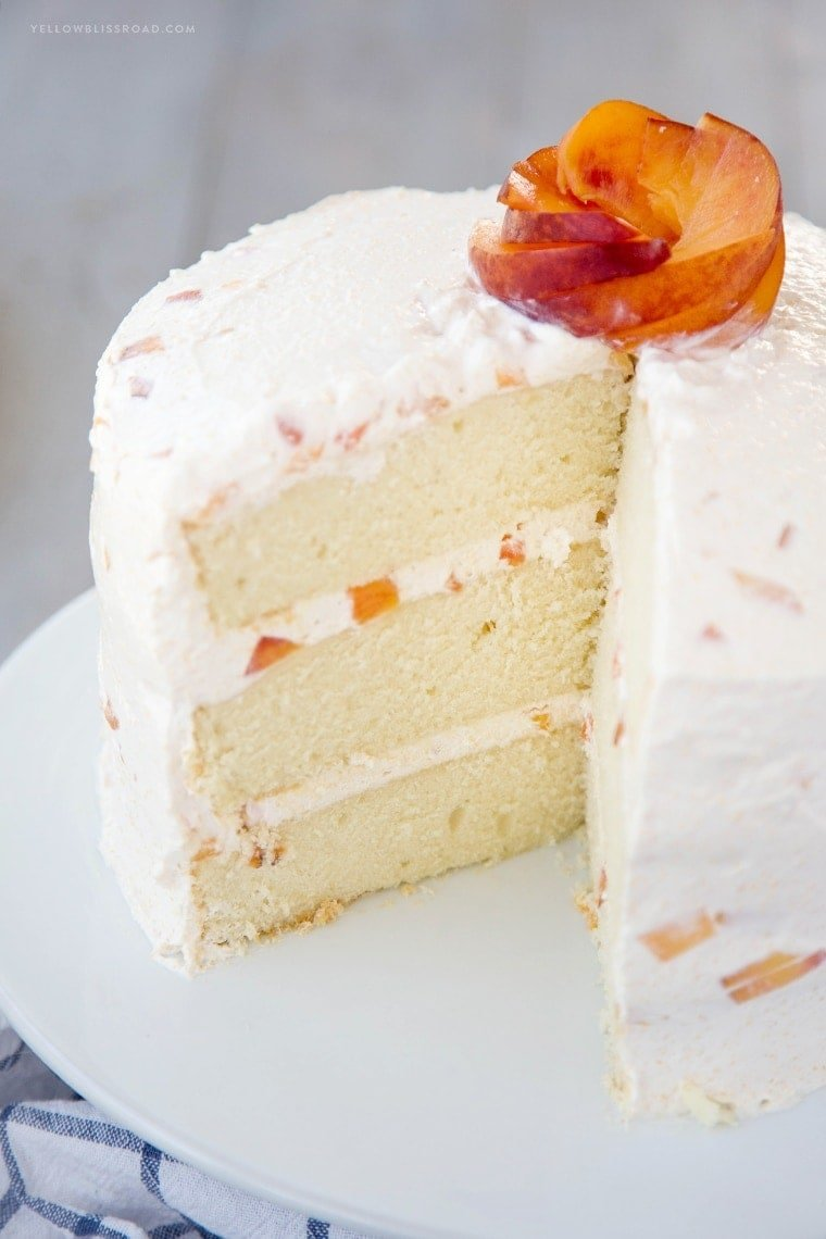 Vanilla Peach Layer Cake is a perfect dessert for summer. Tender, moist cake is layered with a sweet peaches and cream frosting, with chunks of fresh peaches.