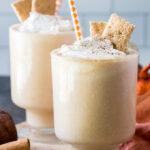 Two glasses filled with pumpkin pie milkshakes