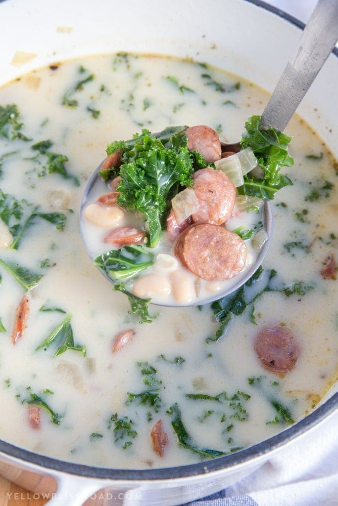 A ladle full of sausage, kale and beans in a creamy broth