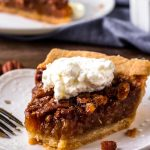 A piece of Pecan pie with whipped cream