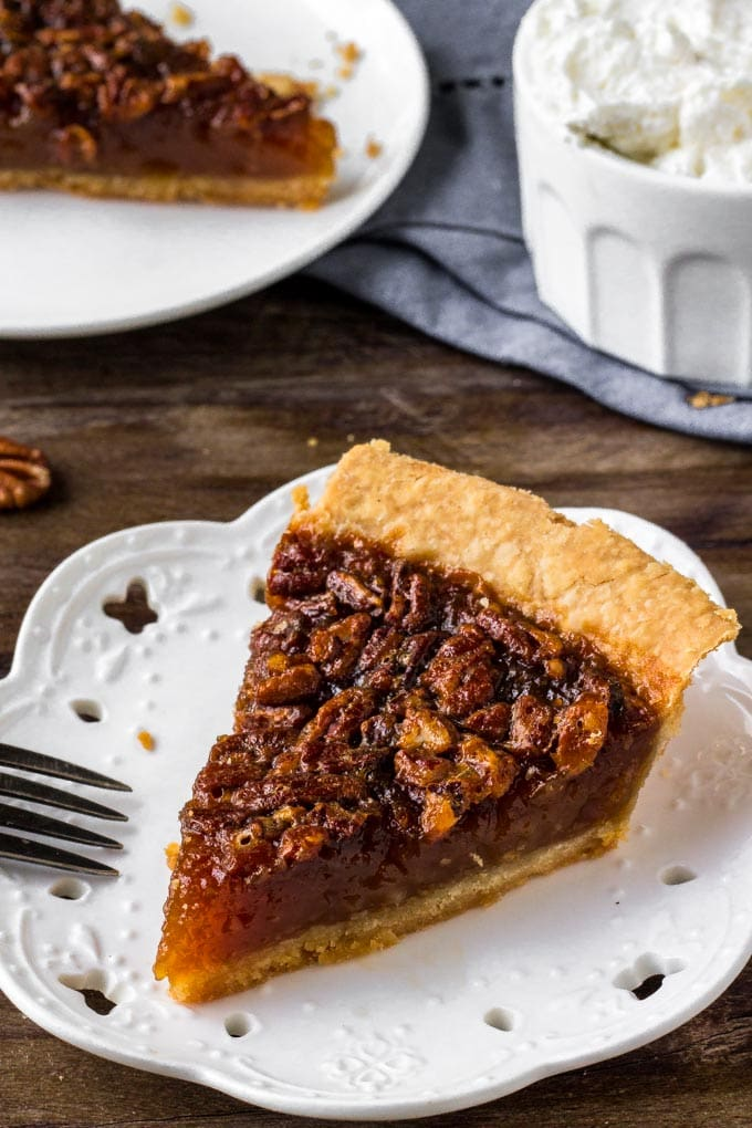 A slice of pecan pie on a white plate.