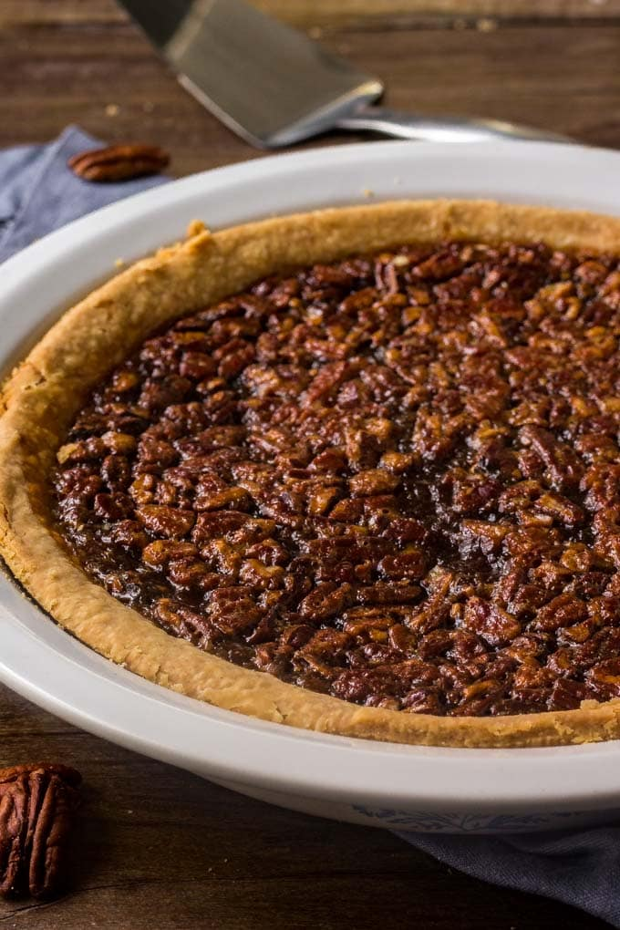 A whole pecan pie in a white pie plate.