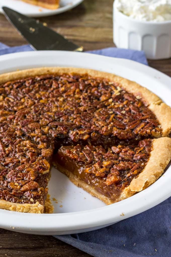 Southern Pecan Pie Recipe with a slice in a pie dish.