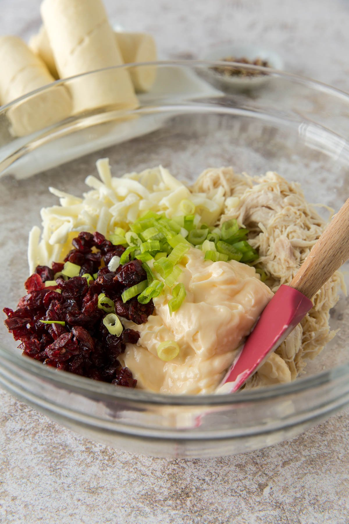 glass bowl, spatula, shredded chicken, mayo, cranberries, cheese, green onion, crescent roll dough
