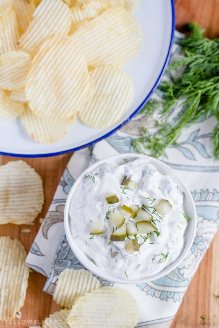 Dill pickle dip in a small bowl and a larger bowl of potato chips.