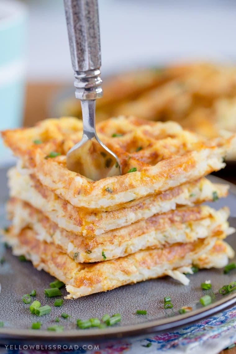 A stack of fresh, crispy Egg & Cheese Hash Brown Waffles with a fork in them.