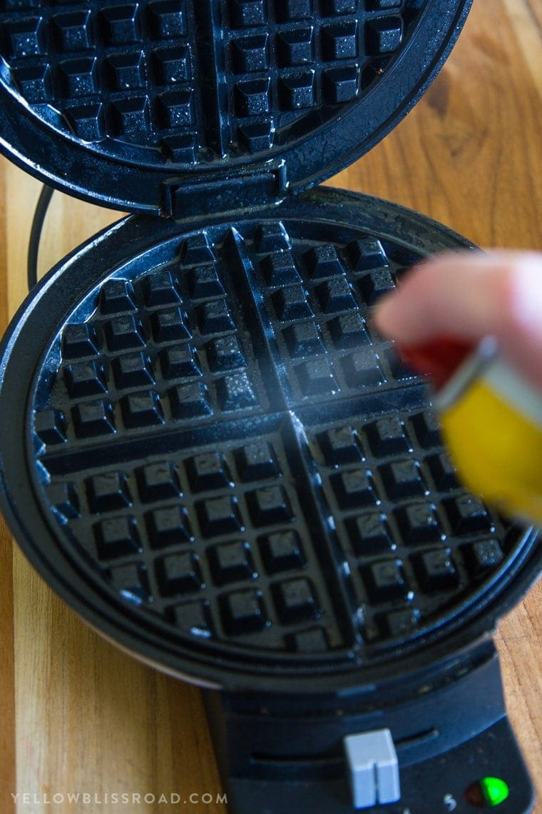 Spraying a waffle maker with nonstick cooking spray for Egg & Cheese Hash Brown Waffles