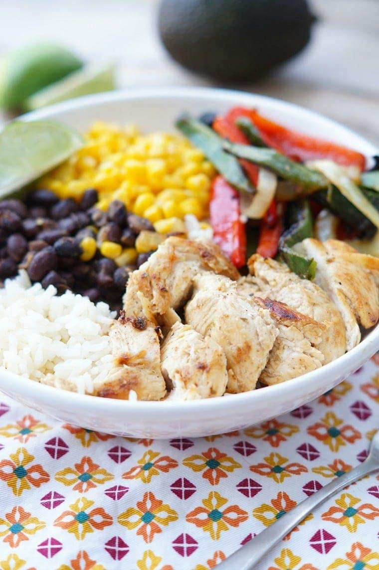 Healthy Chicken Fajita Bowls - Rice covered with fajita-seasoned chicken, peppers and onions, beans and corn. A delicious and easy dinner!
