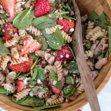 A bowl of pasta salad with strawberries and spinach