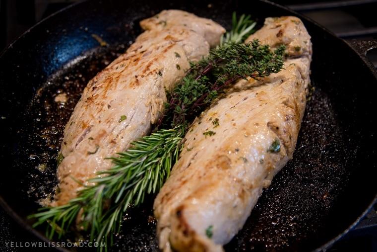 Two cooked pork tenderloins in a pan