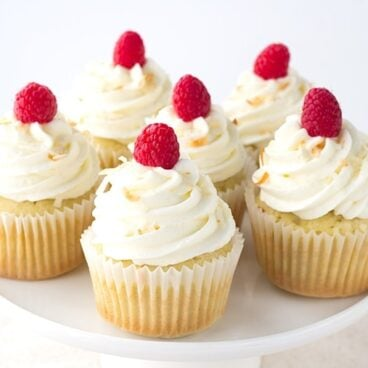 Coconut Cupcakes with a Raspberry Filling - coconut flavored cupcakes filled with a fresh raspberry filling and topped with a delicious coconut frosting and toasted coconut.