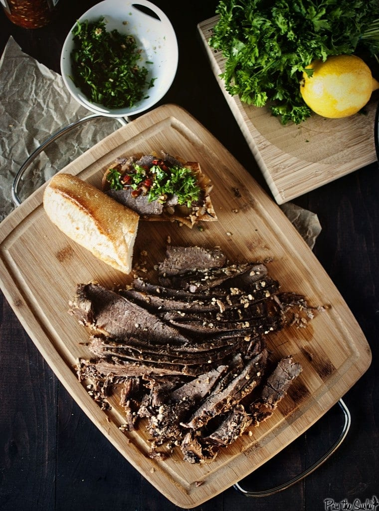 Sliced brisket sitting on top of a wooden cutting board