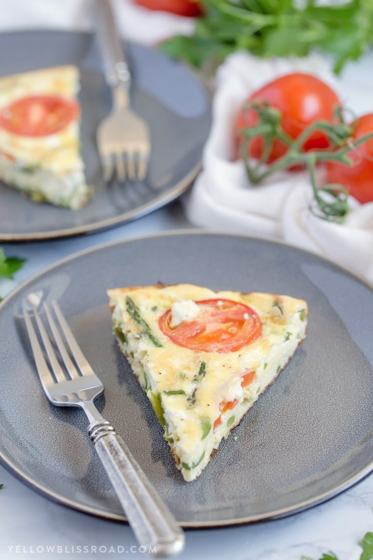 A slice of a tomato and asparagus frittata on a gray plate.