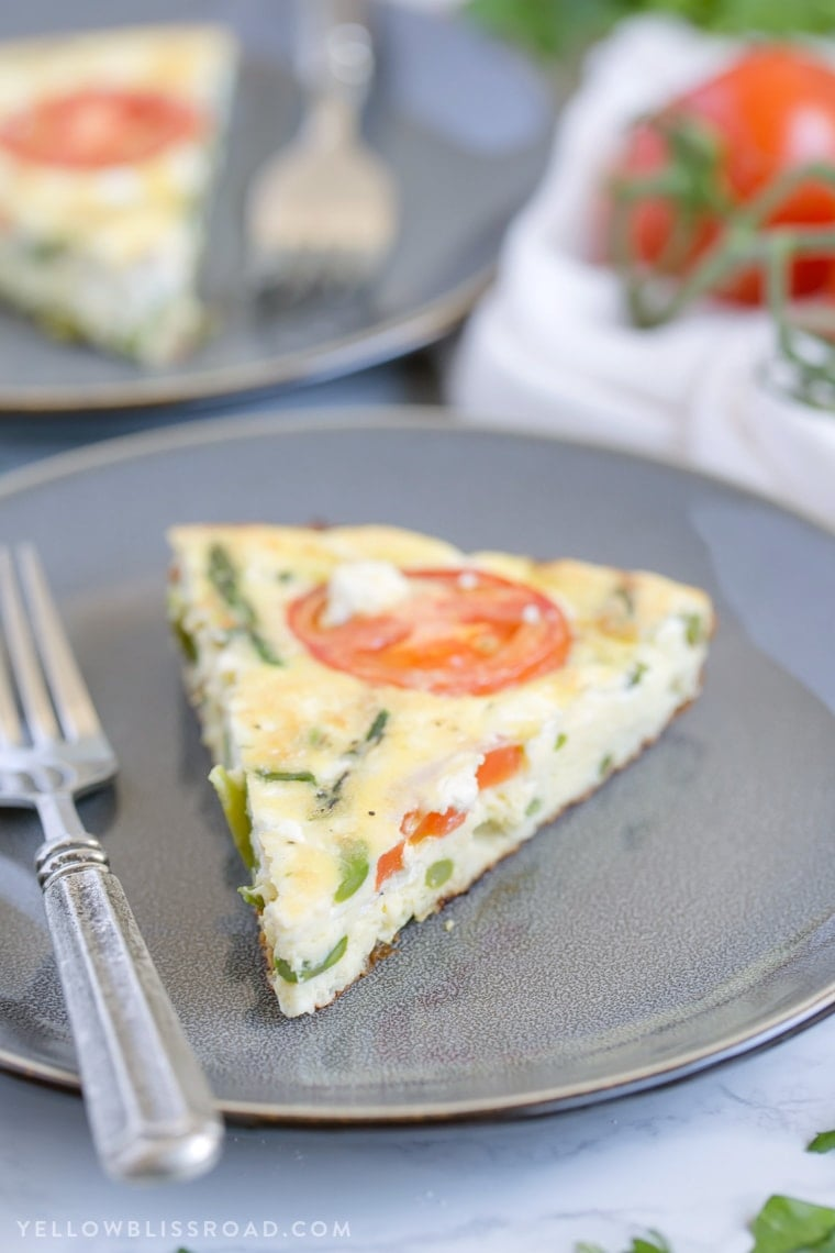 A slice of frittata on a gray plate with a fork