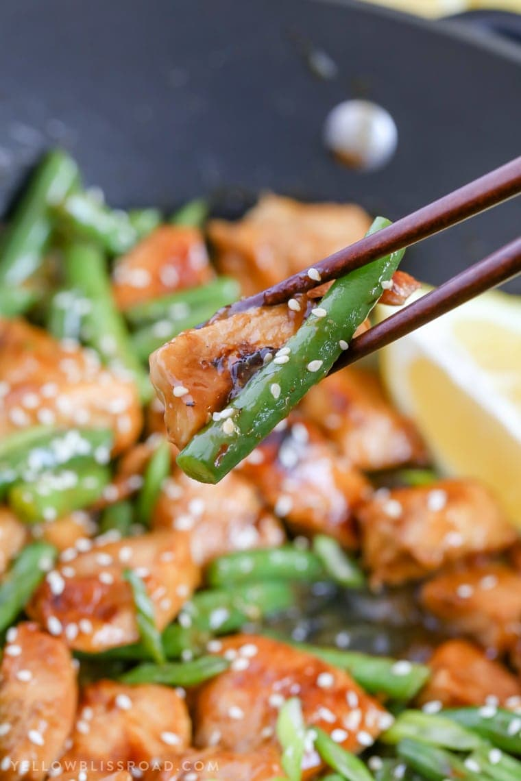 honey lemon chicken and green beans stir fry eaten with chopsticks.