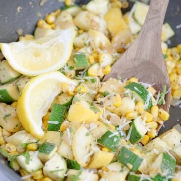 A dish is filled with corn and zucchini