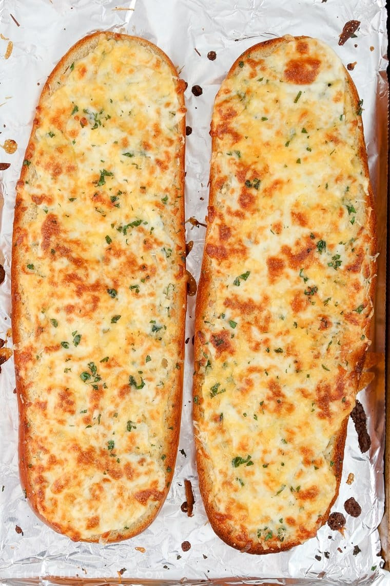 Two halves of cheesy garlic bread - homemade garlic bread with golden browned cheese.
