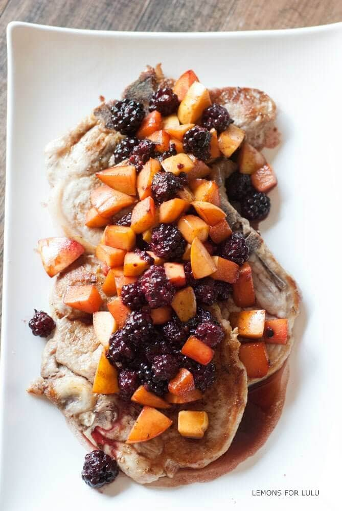 A plate of pork with fruit on top