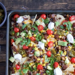 Sheet Pan Nachos are loaded with toppings and are sure to be a great crowd-pleaser!