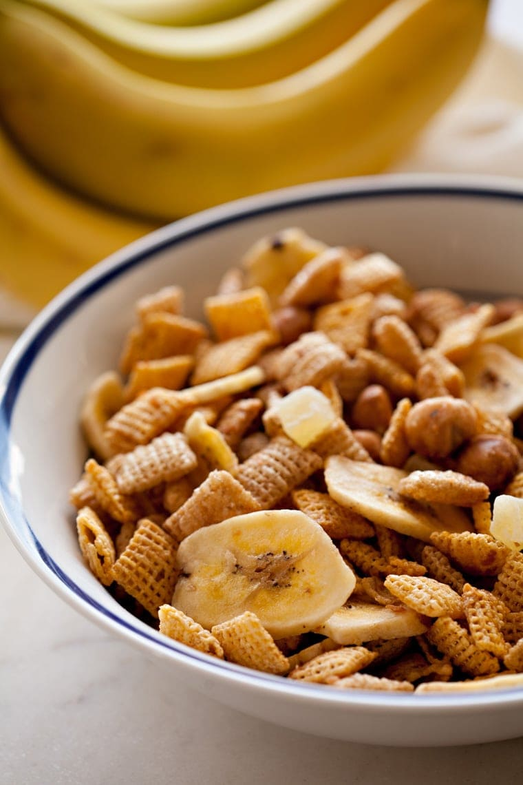 A bowl filled with banana chips, chex cereal and macadamia nits
