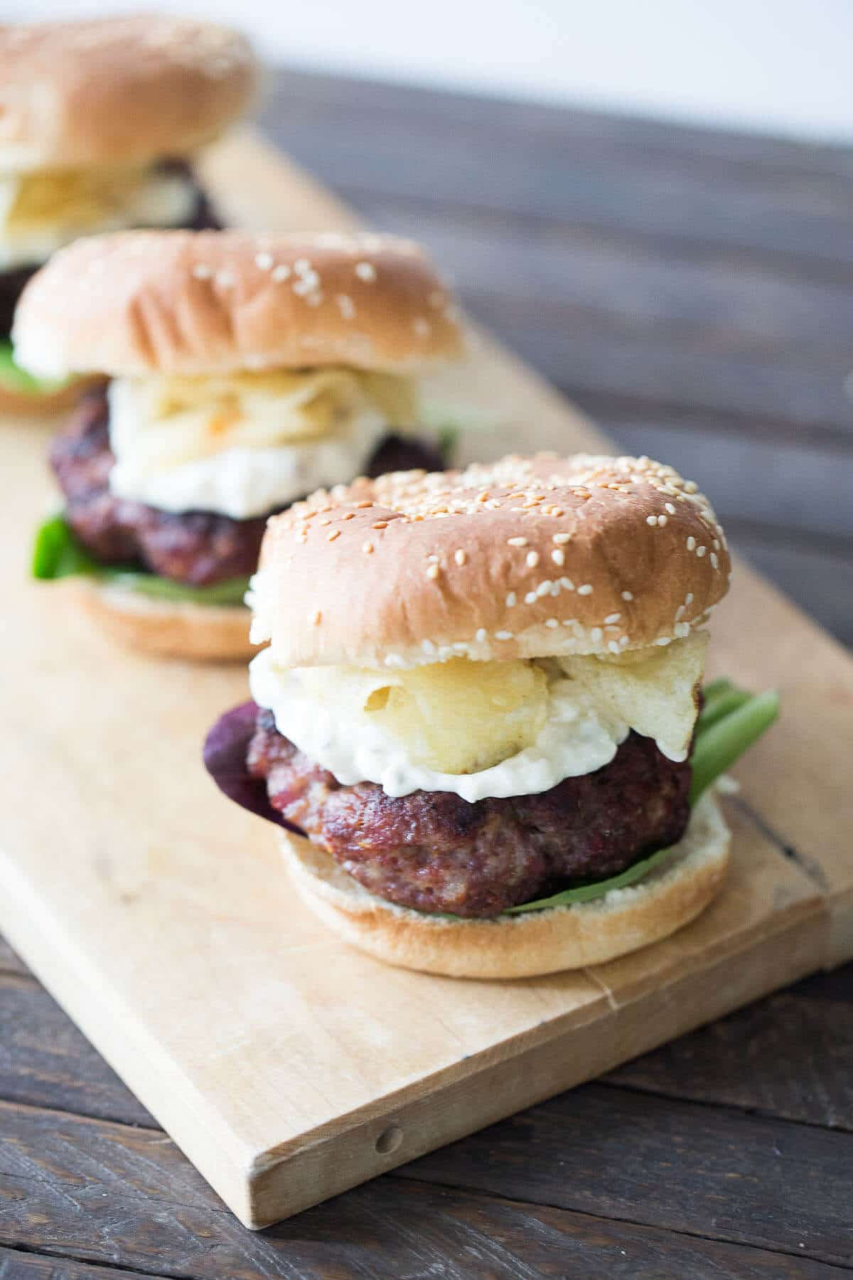 A close up of burgers sitting on top of a wooden cutting board