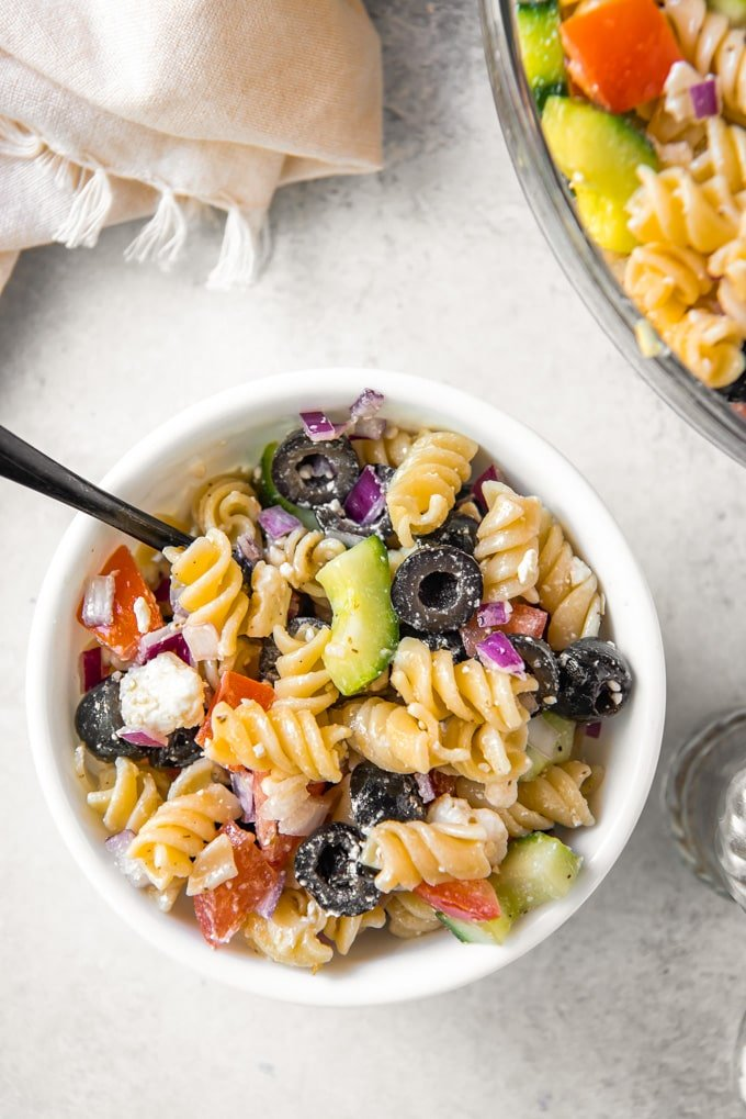 A bowl of greek pasta salad with a spoon.