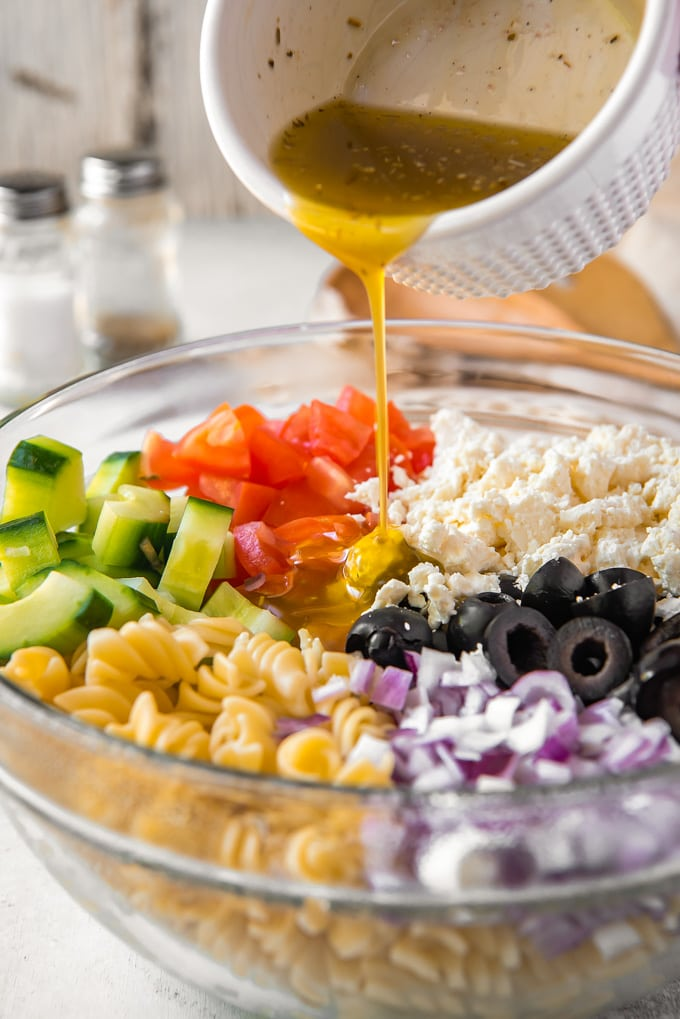 Ingredients to make greek pasta salad in a bowl with dressing being poured on.