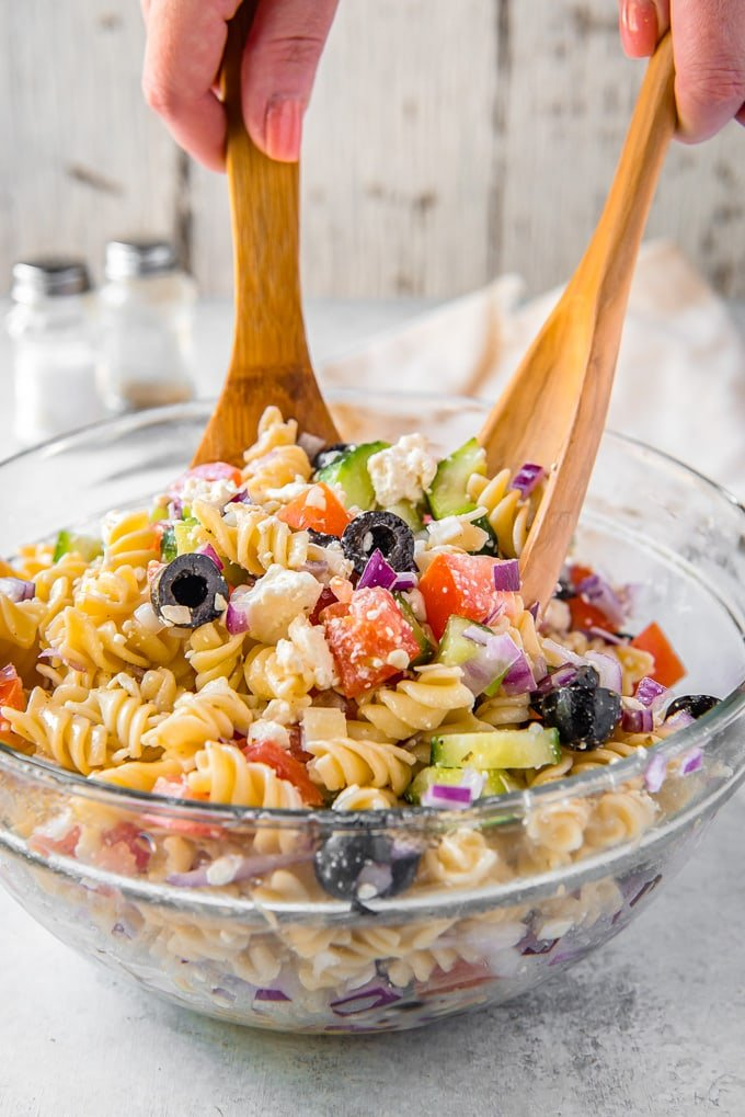 Greek pasta salad in a large bowl being tossed with salad tongs.