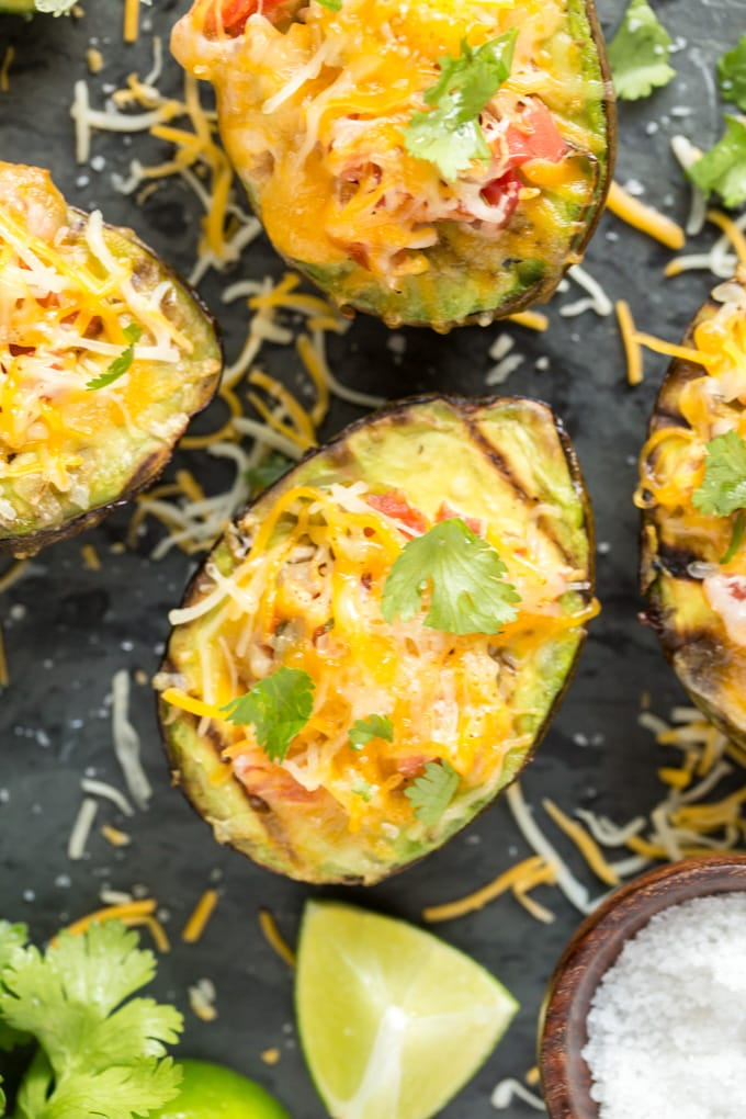 Grilled avocados on a black background topped with cheese, salsa and cilantro. A small bowl of coarse salt and some sliced limes surround them.