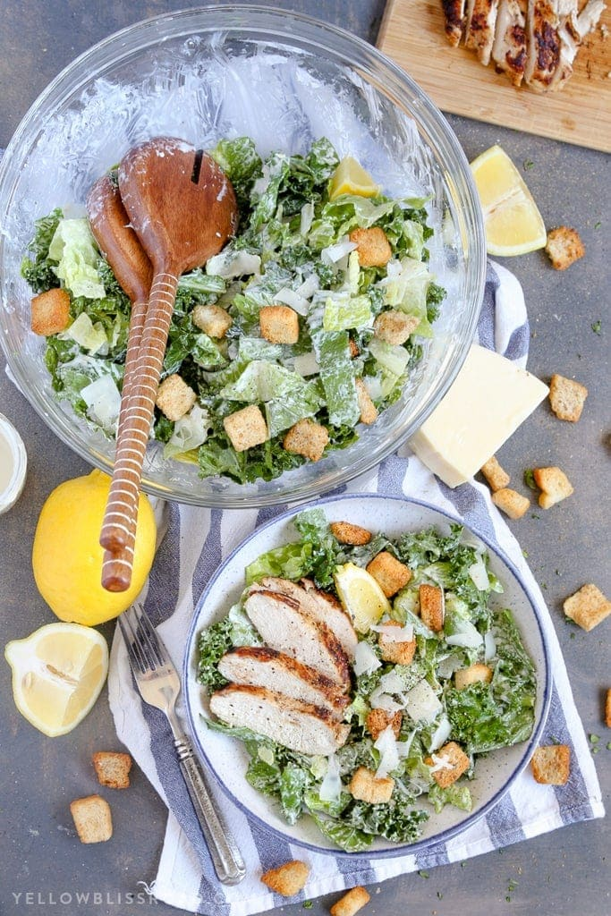 a large bowl of caesar salad, a small bowl ow casear salad with slices of chicken, a blue and white napkin and lemon slices.