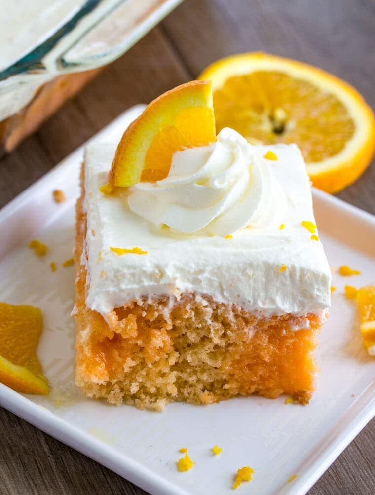 Slice of Orange Creamsicle Poke Cake with Whipped Cream Topping