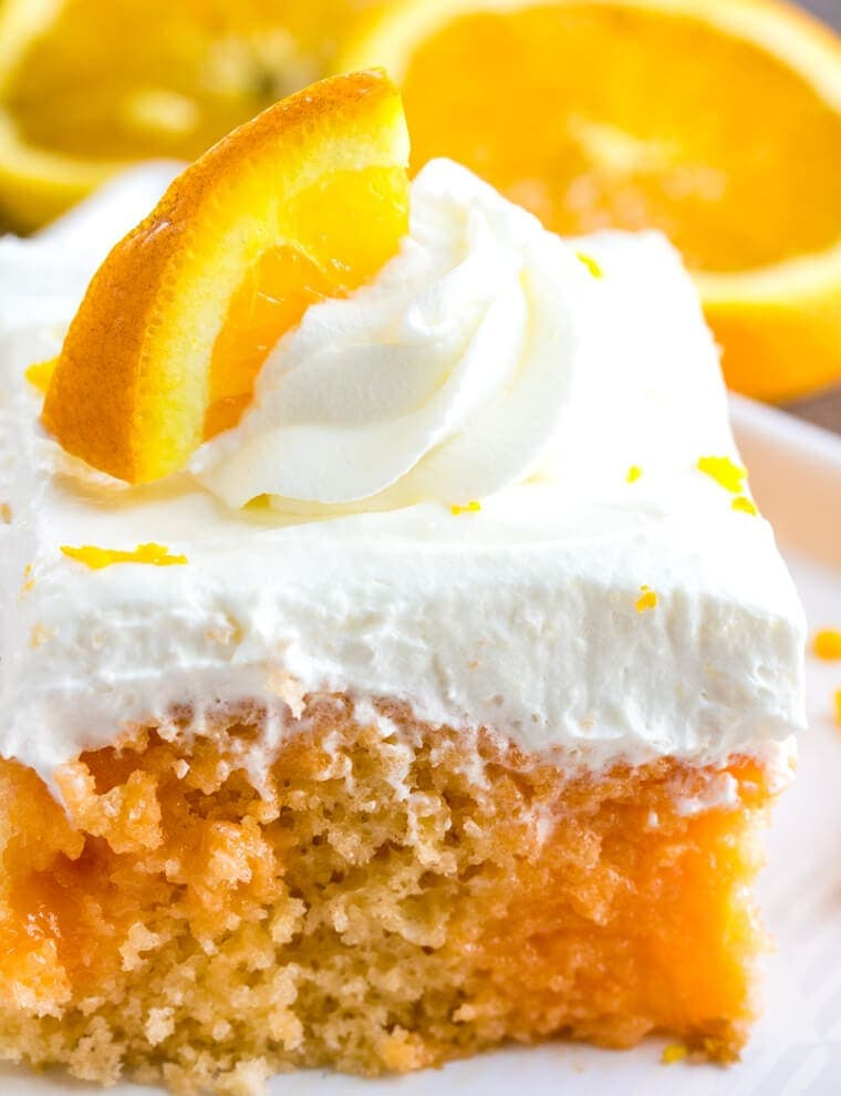 Orange Creamsicle Poke Cake with Whipped Cream Topping and orange slice