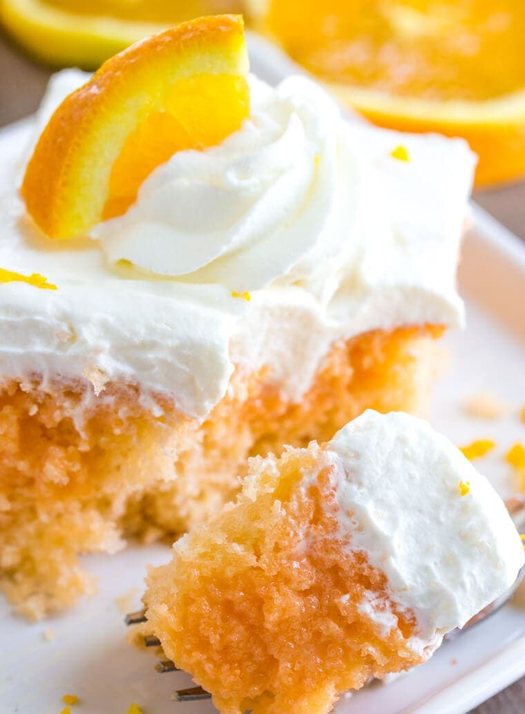 Close up bite of Orange Creamsicle Poke Cake with Whipped Cream Topping