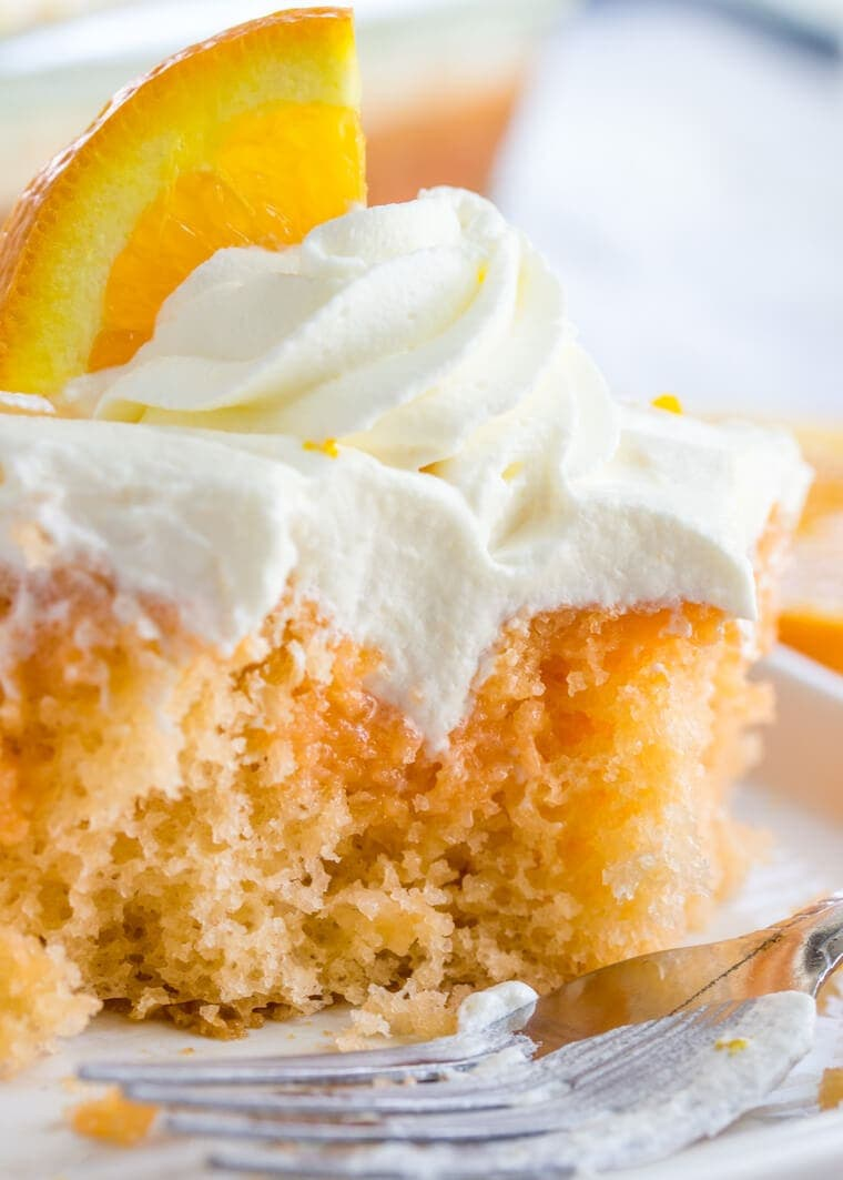 Close up slice of Orange Creamsicle Poke Cake with Whipped Cream Topping