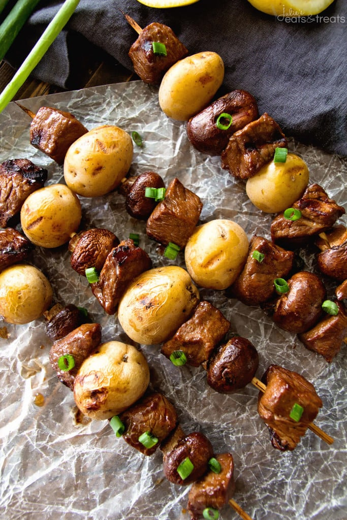 A close up of steak and potato kebabs